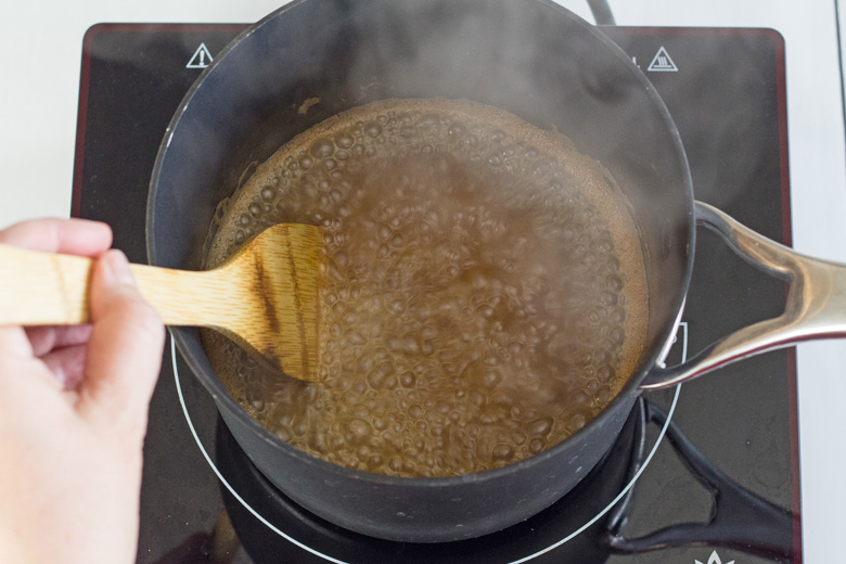 apple cider syrup simmering in a saucepan