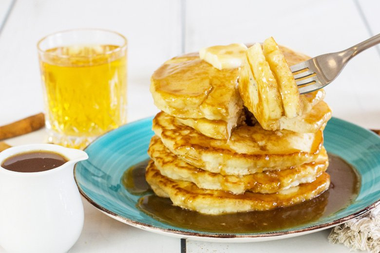 bite being taken out of a stack of pancakes with syrup
