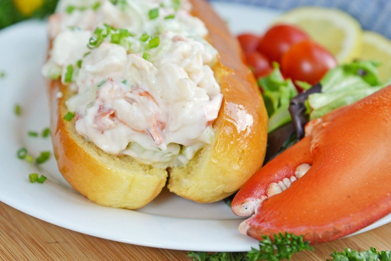 side view of cold lobster roll on split top bread