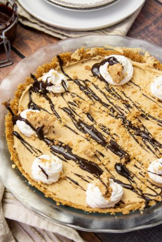 angle of peanut butter pie with whipped cream topping