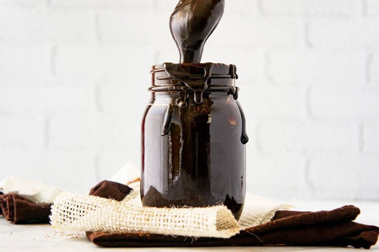 homemade fudge sauce on burlap in a mason jar