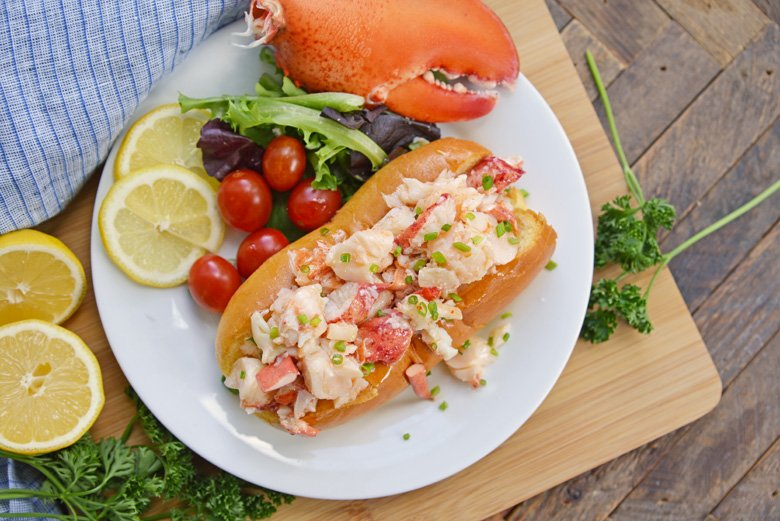 overhead of hot lobster rolls with salad and lobster claw