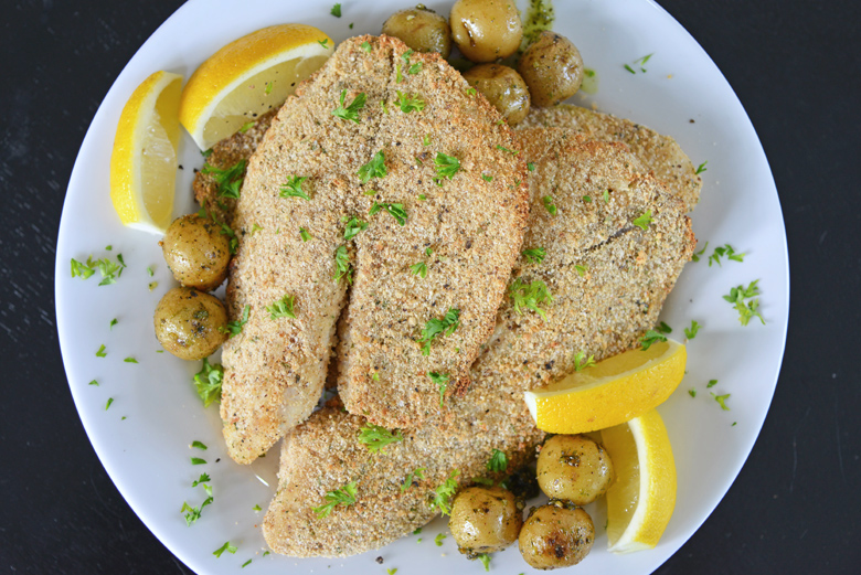 overhead of parmesan tilapia with lemon wedges