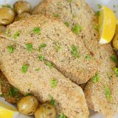 A plate of breaded tilapia with lemons and parsley