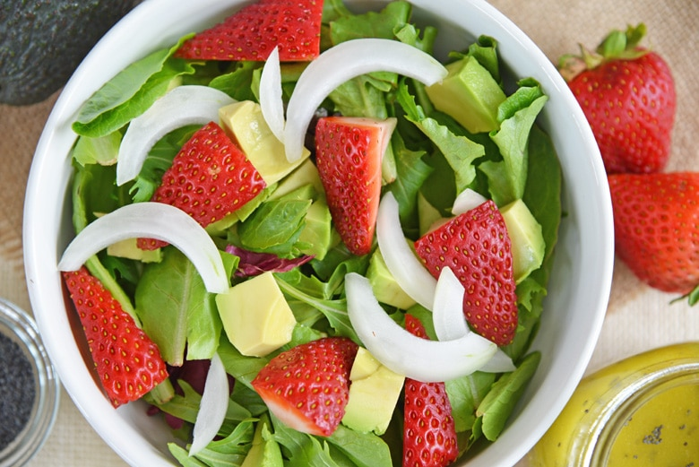 close up of strawberry salad with avocado and onion slices