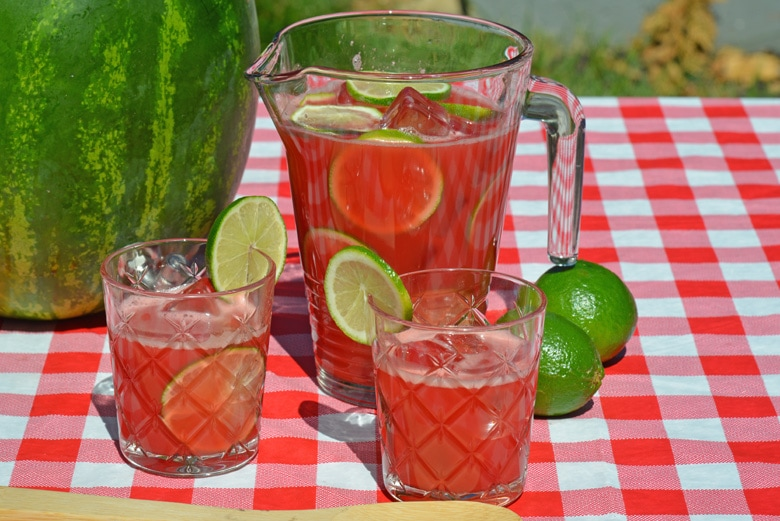 pitcher and two glasses of vodka watermelon cocktail on a red checkered tablemat