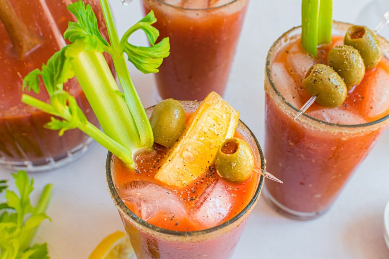 overhead of bloody mary with celery, lemon and olive garnish