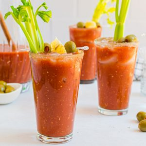 three glasses of bloody mary with garnish