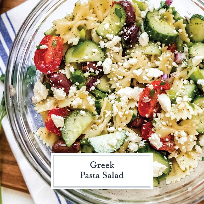 greek pasta salad with feta cheese, tomatoes, cucumber and olives in a glass mixing bowl