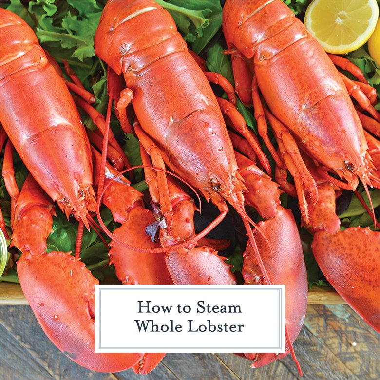 three steamed lobster lined up on lettuce with lemons and drawn butter
