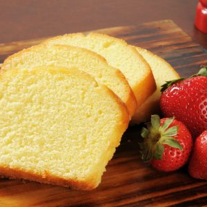 slices of pound cake with fresh strawberries on a wood cutting board