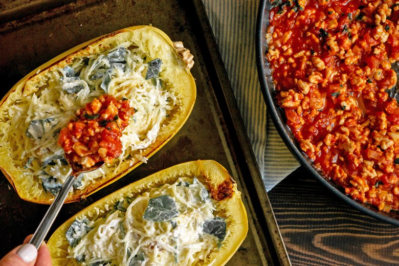 spooning ground beef mixture onto spaghetti squash lasagna