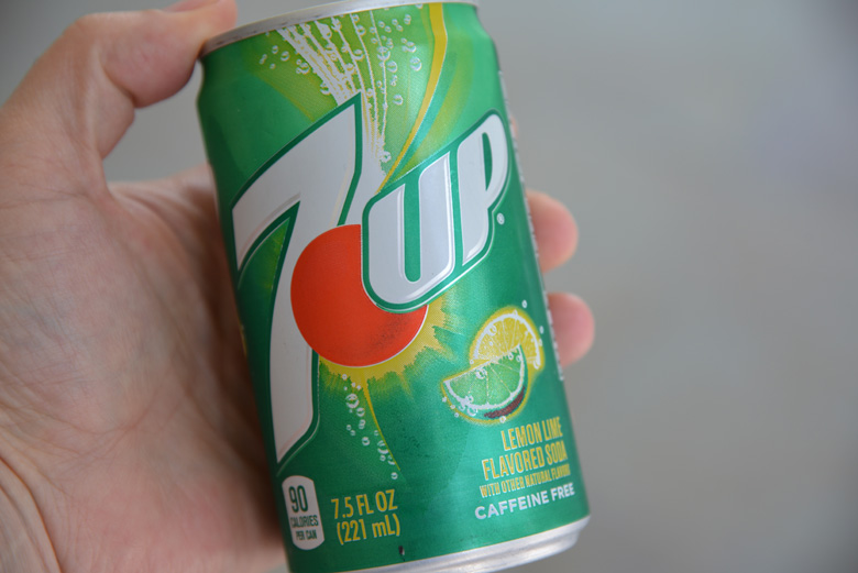 small can of 7 up being held