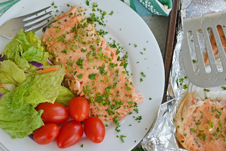 salmon filet on a white plate with salad
