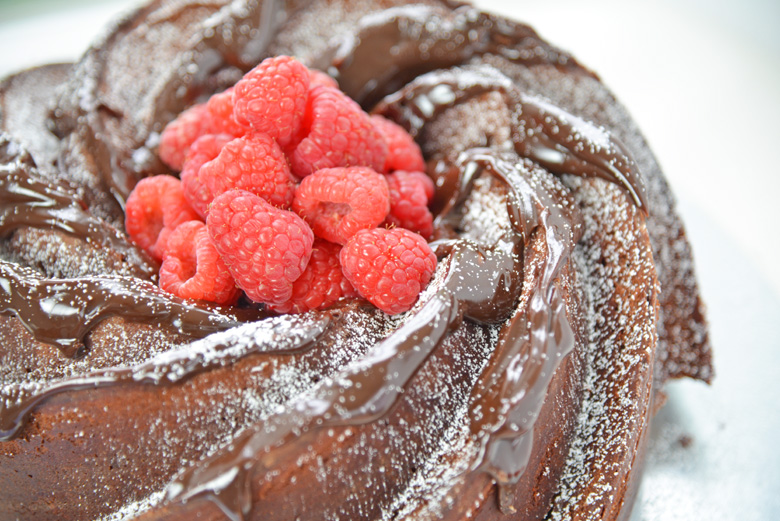 side angle view of chocolate bundt cake dripping with fudge sauce