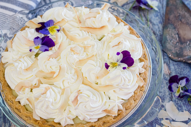 angle of coconut cream pie on blue table