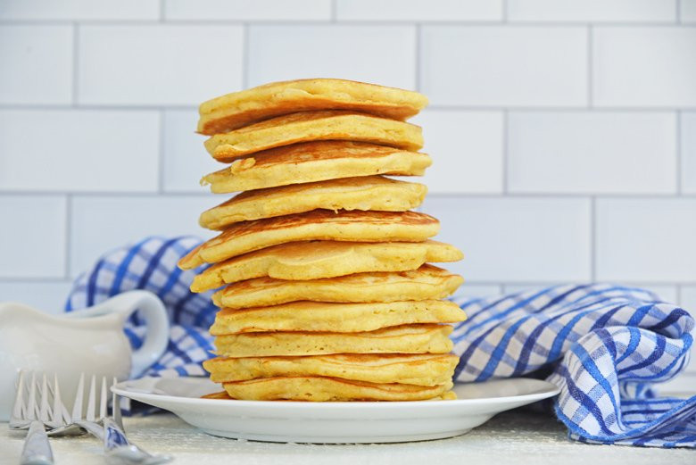 tall stack of corn cakes on white plate