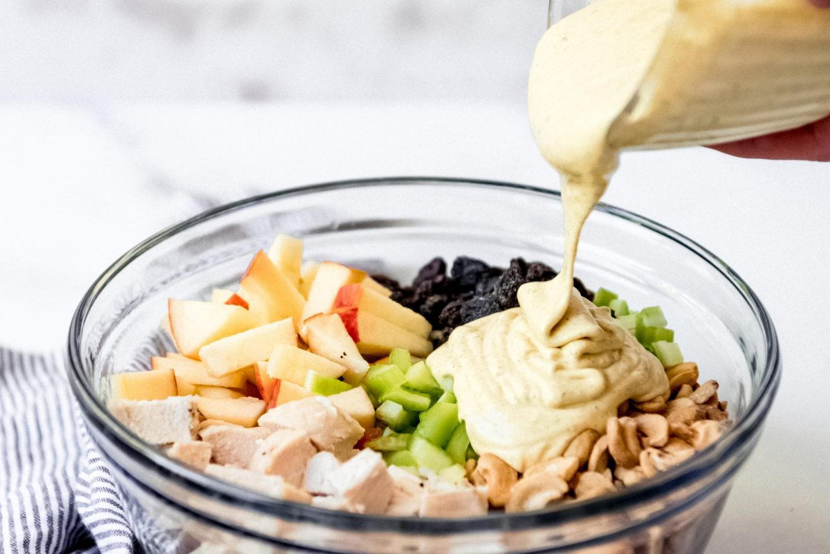 creamy dressing pouring on chicken salad
