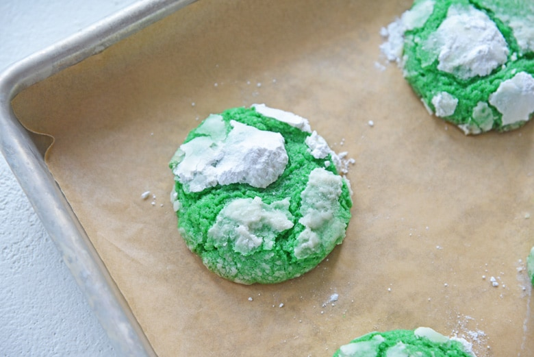 mint crinkle cookie on parchment paper on a baking sheet