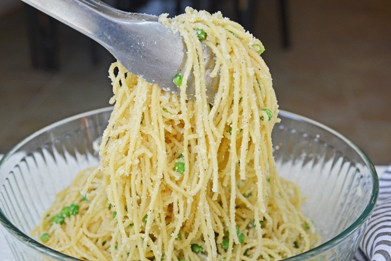 tongs holding spaghetti with cheese