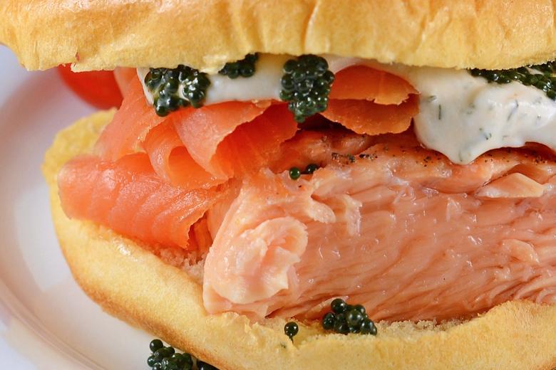 close up of salmon sandwich with smoked salmon, fresh salmon, caviar and caviar