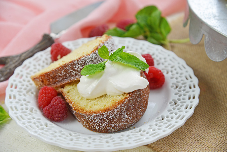sour cream pound cake slices with whipped cream and berries