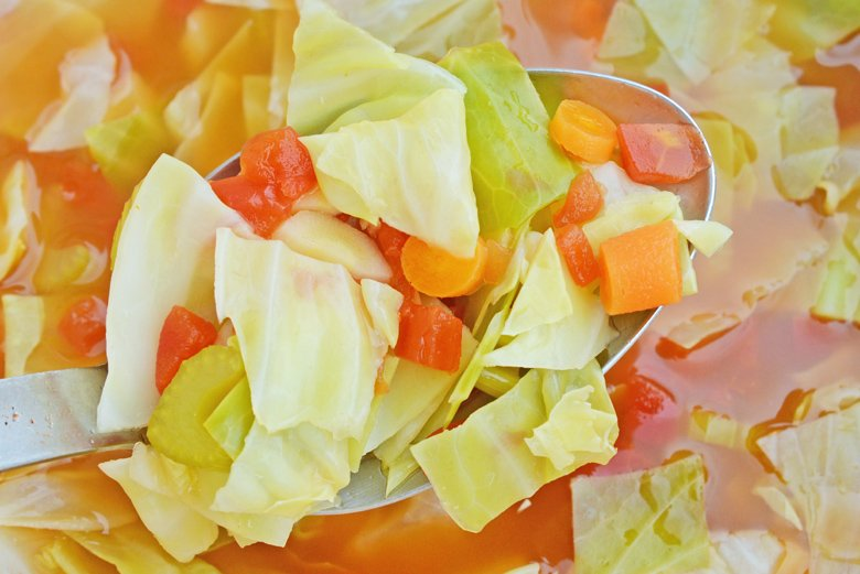 Close up of cabbage soup in a large spoon