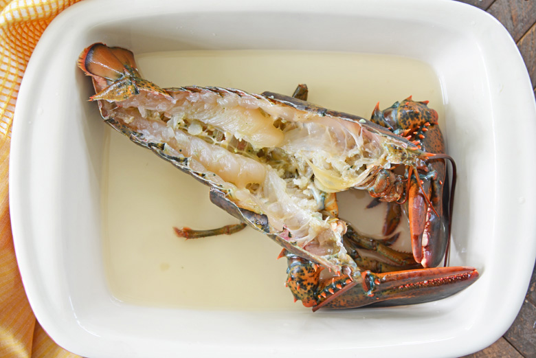 halved lobster in a baking dish