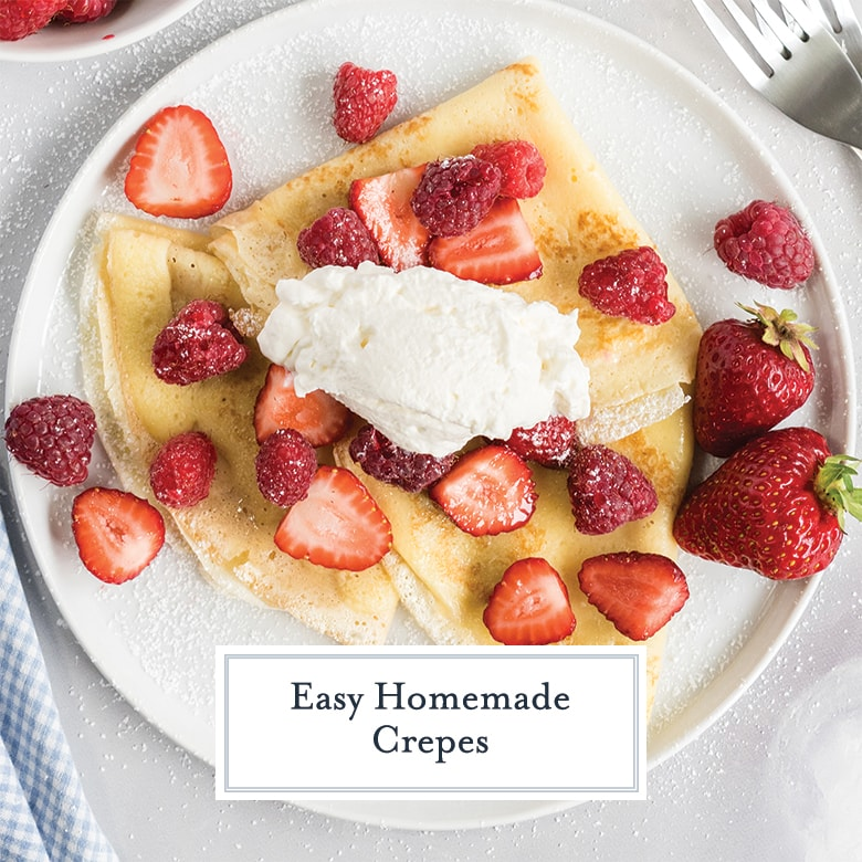 overhead of crepes with fresh berries, whipped cream and powdered sugar