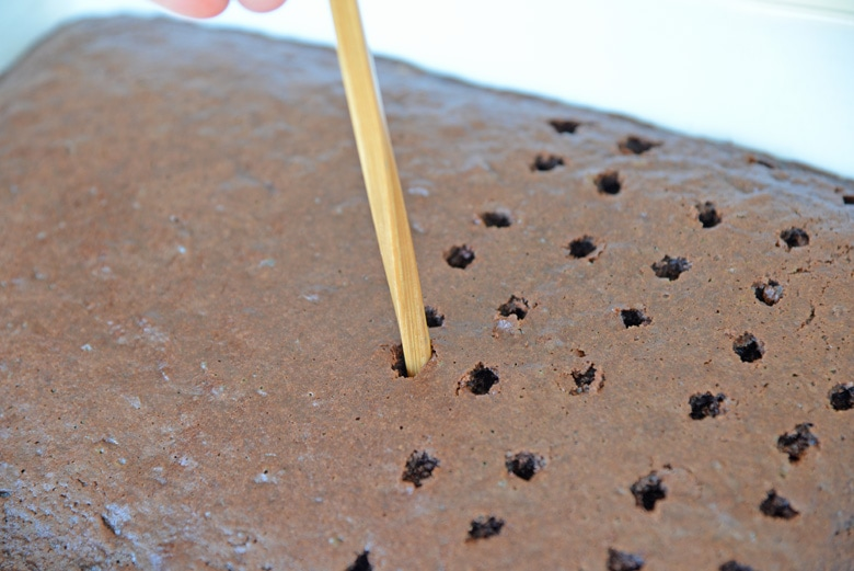 chopstick poking holes in a chocolate cake