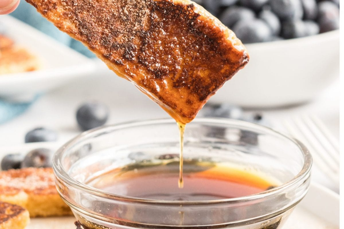 french toast dipping into syrup