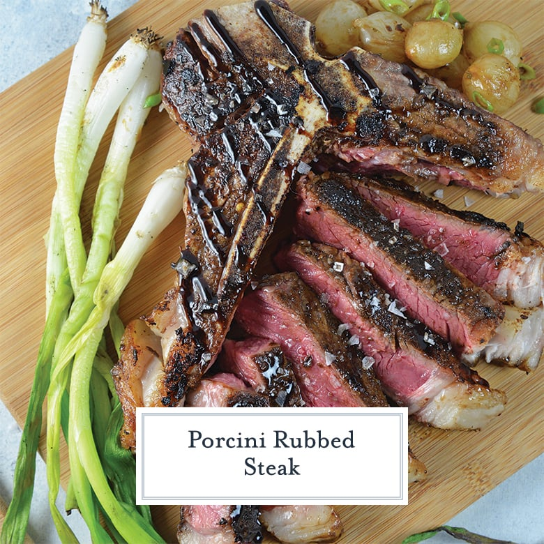 carved t bone steak on a cutting board with onions