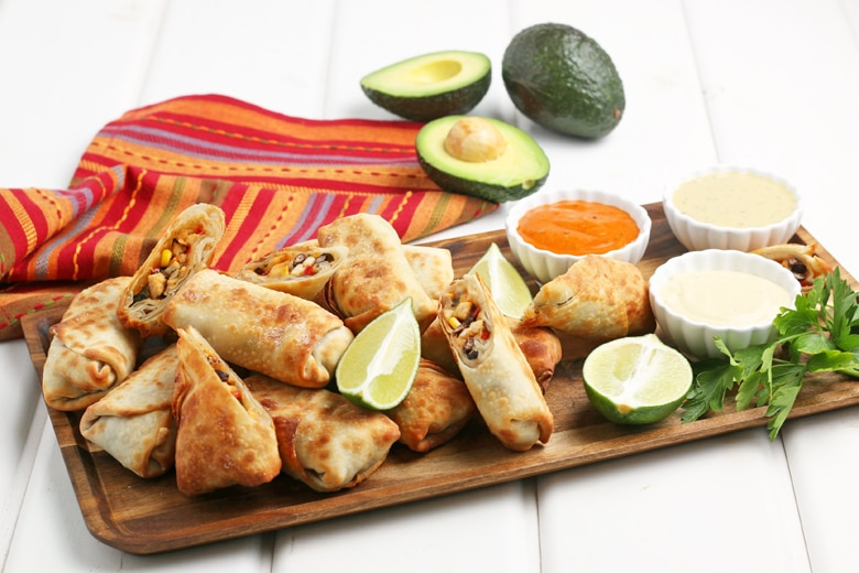 southwest egg rolls on a serving platter with dipping sauces