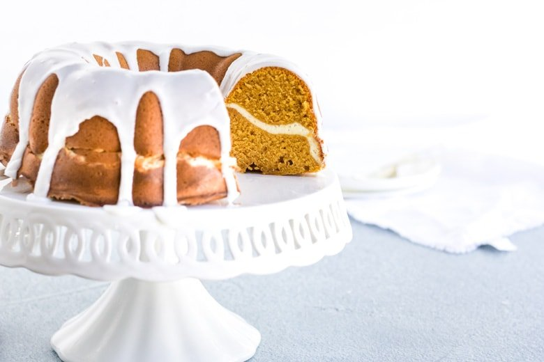 pumpkin cream cheese pound cake with icing on a cake plate