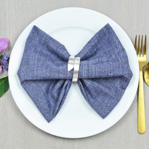 bow tie napkin fold on a blue napkin