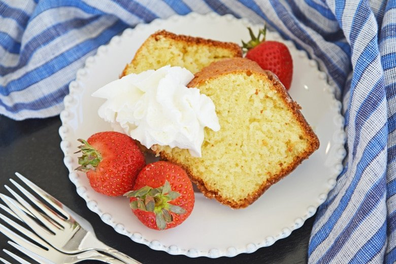 two slices of butter cake, strawberries and whipped cream