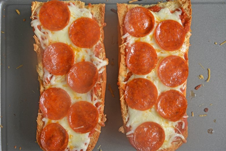 two slices of pepperoni french bread pizza on a baking sheet