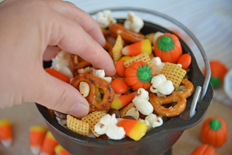 hand reaching into snack mix in a black cauldron