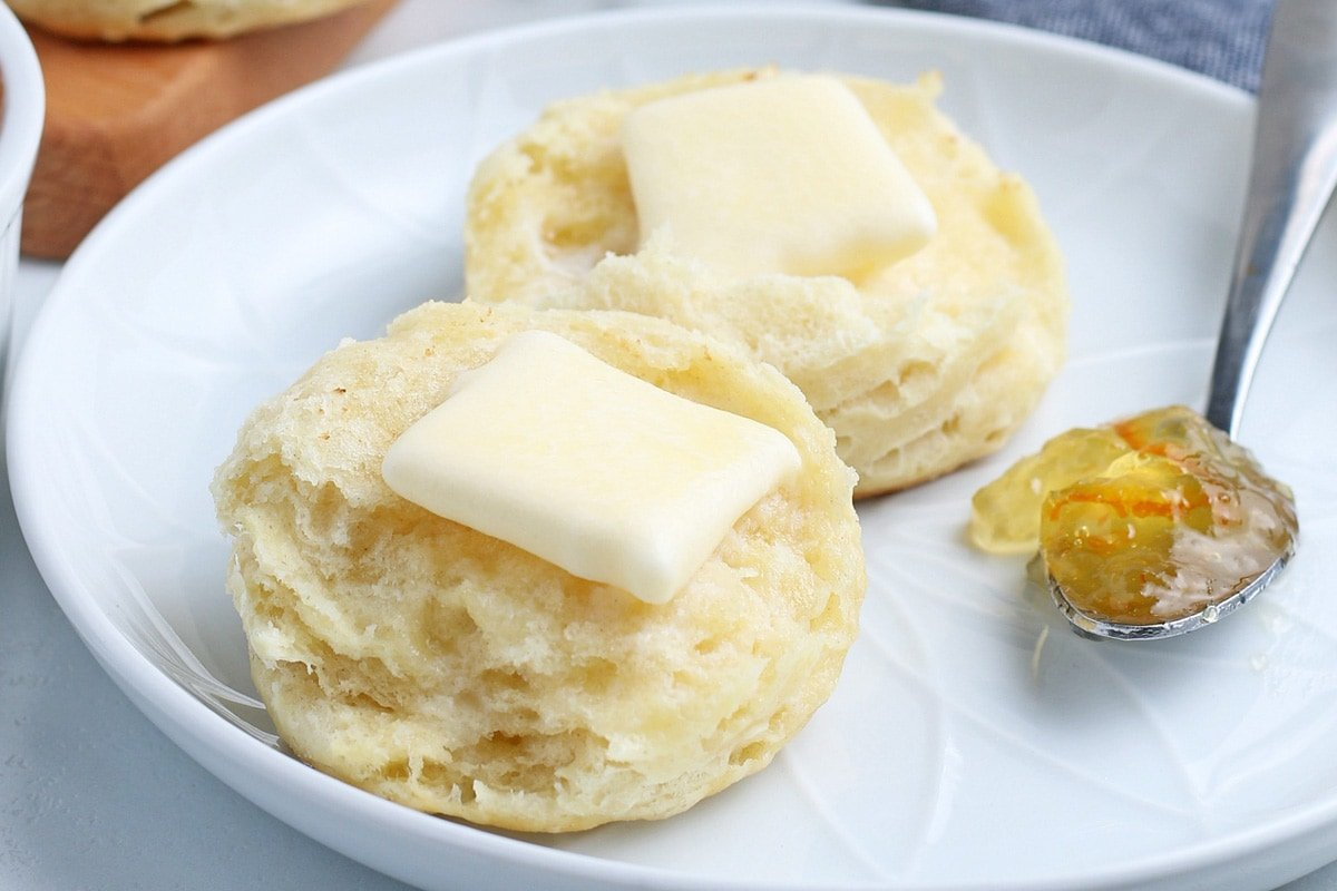 close up of buttered biscuit with jam
