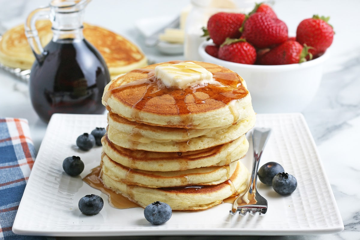 stack of DIY pancakes with fruit and syrup