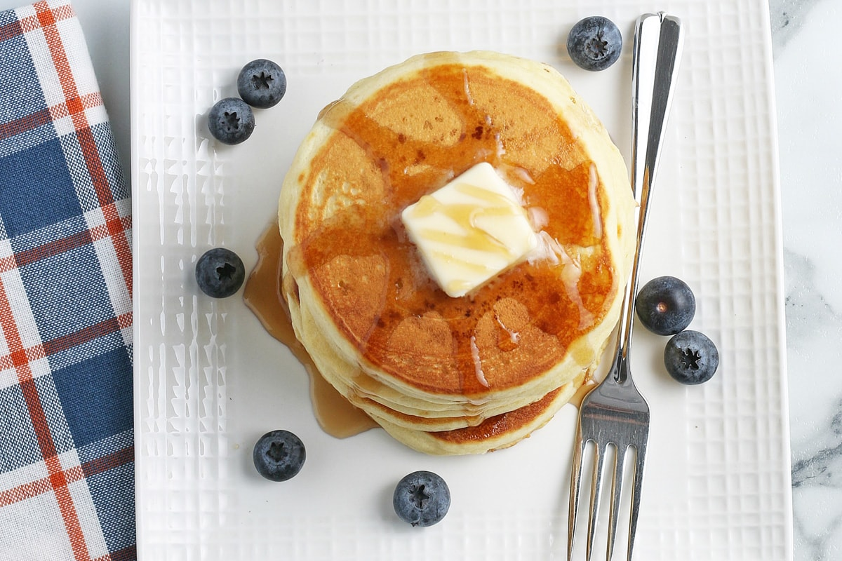 overhead of a stack of pancakes with fruit, butter and syrup