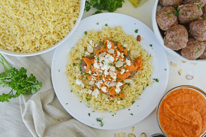 overhead of lamb meatballs with orzo and sauce
