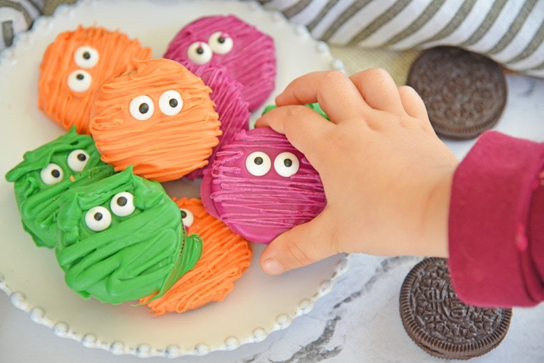 child's hand reaching for a mummy cookie