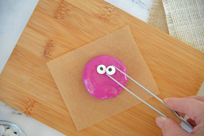 placing candy eyeballs on a chocolate covered oreo