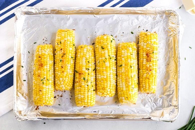ears of corn on a rimmed baking sheet