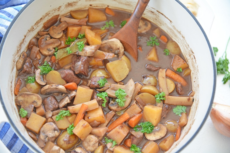 wooden spoon in a pot of red wine beef stew