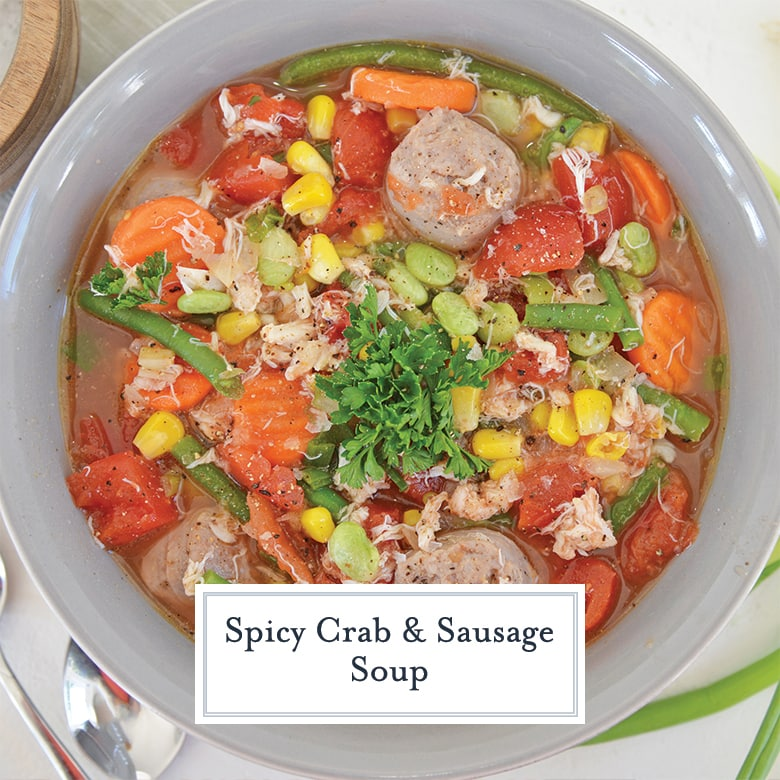 overhead of crab and sausage soup with vegetables in a gray bowl