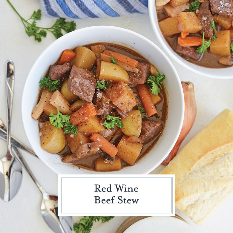 overhead of two bowls of beef stew with red wine and bread