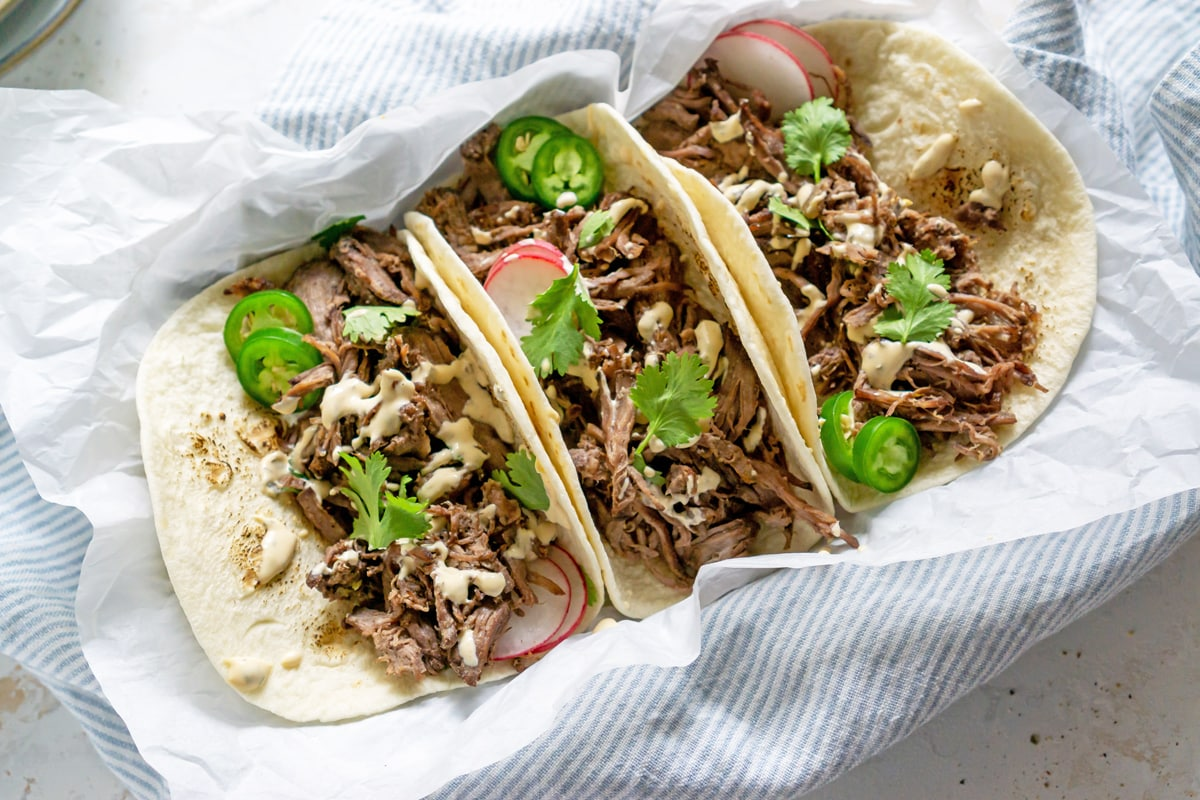 three tacos with jalapenos and cilantro