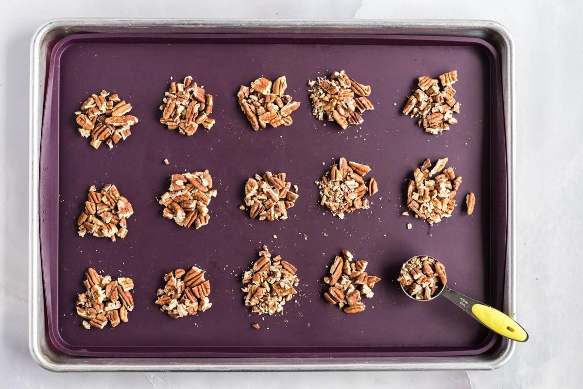 pecan piles on a baking sheet
